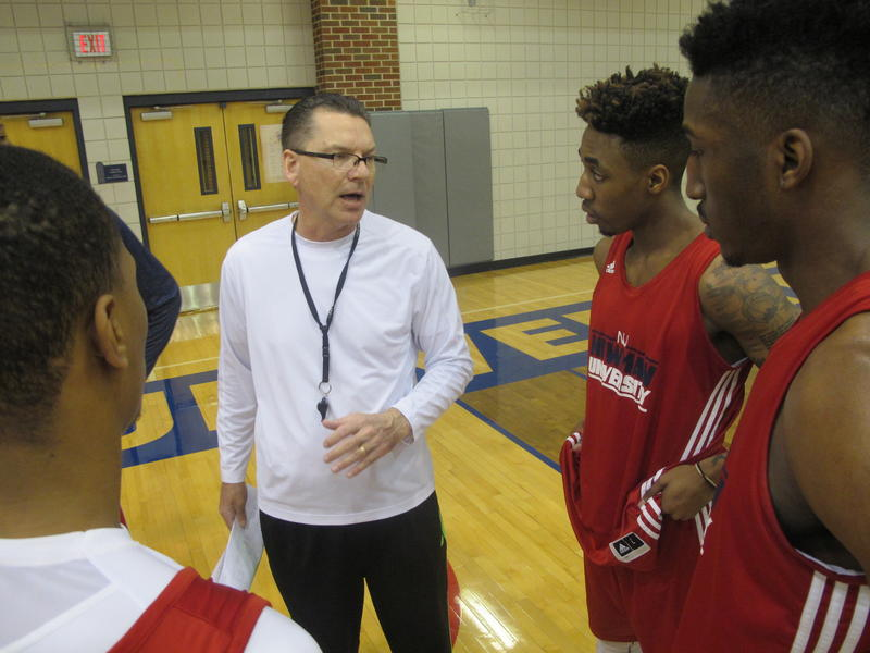 Mark Potter, center, speaks to members of the Newman University basketball team during a practice last year.