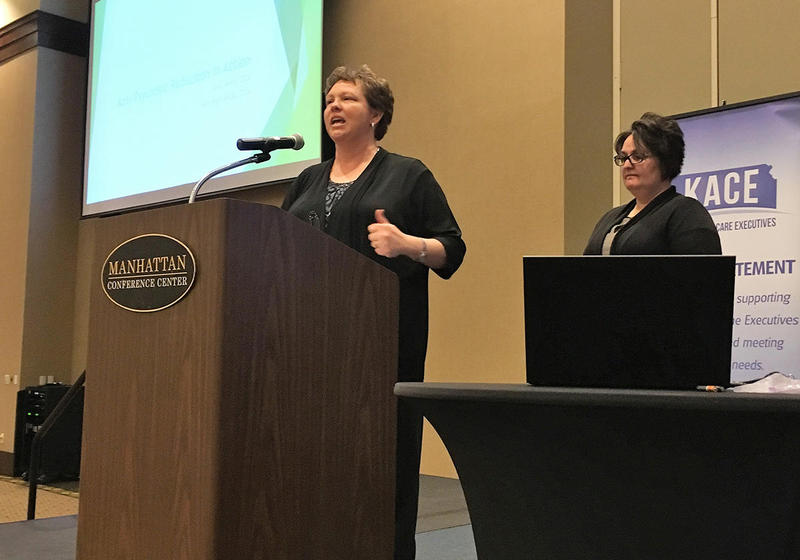 Janell Wohler, the administrator of Linn Community Nursing Home, speaks at a conference of fellow administrators about reducing use of antipsychotics among patients. At right is Kate Rieth, director of nursing at the facility.