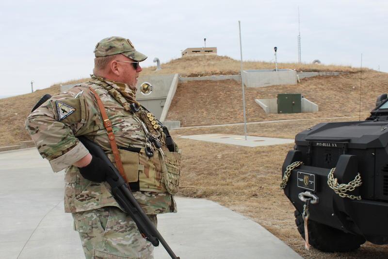 A guard patrols the perimeter of a survival bunker near Concordia, Kansas.