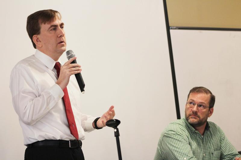 Libertarian Chris Rockhold, left, speaks during Saturday's Q&A at Sunflower Community Action as Democrat James Thompson looks on.