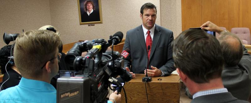 Secretary Kobach speaks to reporters last year