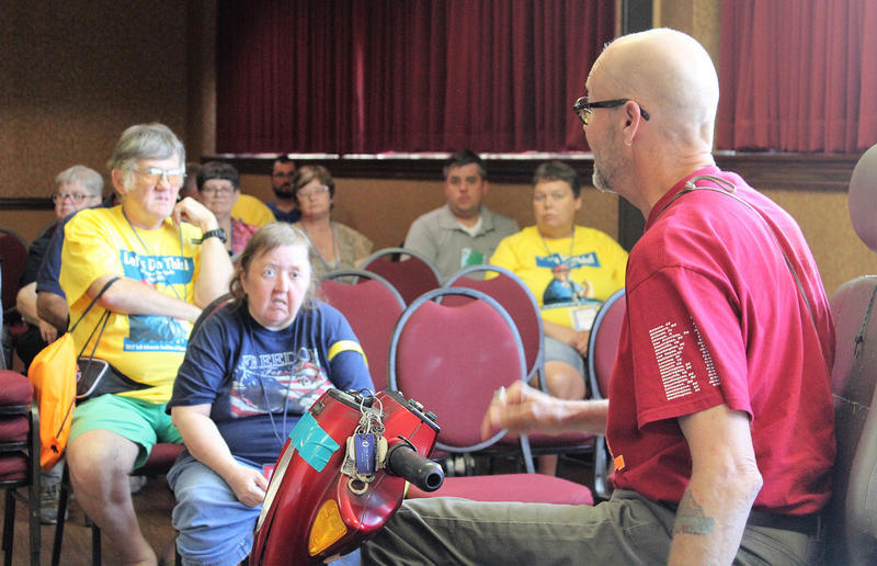 Mike Oxford, director of the Topeka Independent Living Resource Center, speaks to disability advocates in Topeka after returning from Washington, D.C., where he was arrested during a protest of the new Senate health bill.