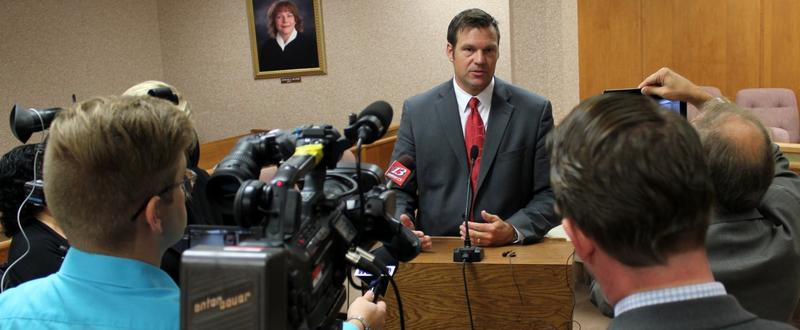 Secretary of State Kris Kobach speaking to reporters last year.