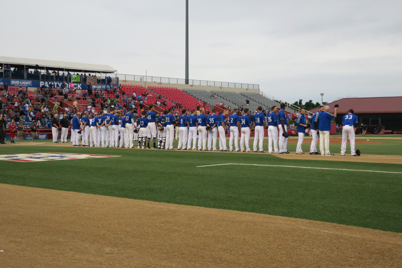 "The Merchants of Everett, Wa., line up along the first baseline for the ""Star Spangled Banner"" prior to their game against the Kansas Stars."