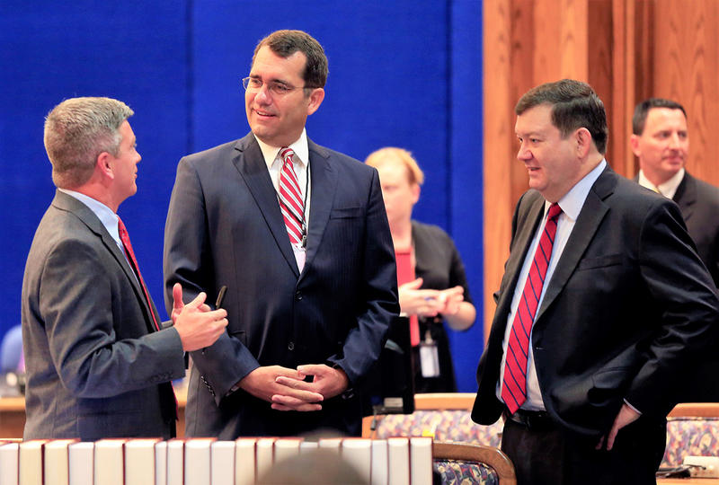 Jeff King, left, an attorney for the Kansas Legislature, talks with Attorney General Derek Schmidt, middle, and Stephen McAllister, attorney for the state. They spoke at a July hearing before the Kansas Supreme Court in the school funding case.