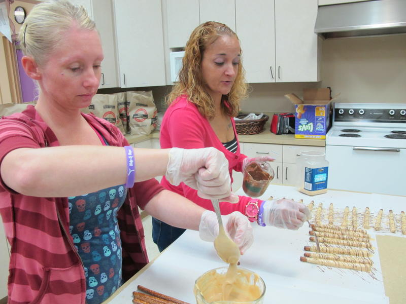 Two participants in the Wichita Women's Initiative Network (WIN) program dipped pretzels sold in retail stores in support of the WIN programs.