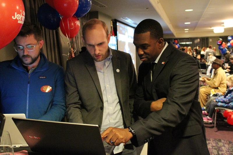 Brandon Johnson, right, reviews election night results with supporters John Moeder, center, and Levi Henry. Johnson says he wants to engage more young residents.