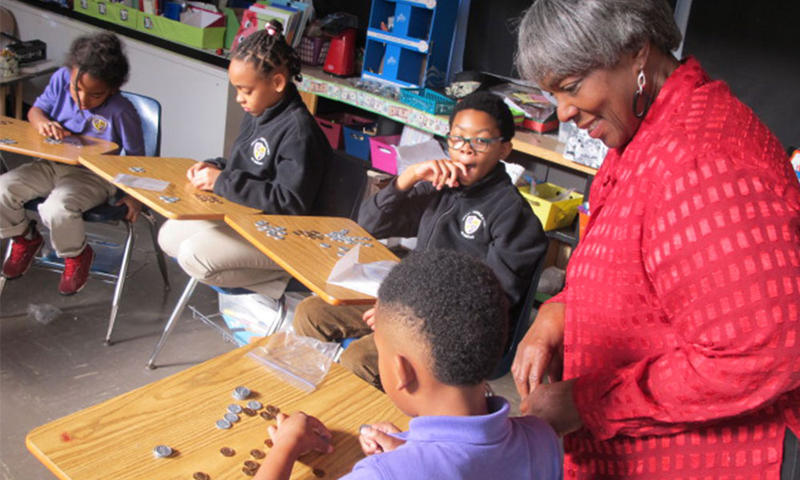 Volunteer and financial literacy educator Bernestine Williams teaches students at Wichita's Urban Preparatory Academy about various ways to count money.