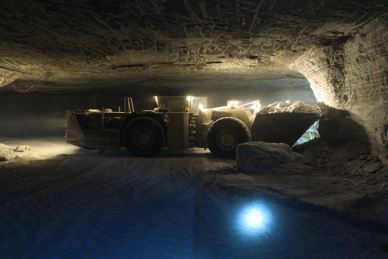 A flattened front-end loader moves blasted salt material from the mine face to a series of crushers and conveyor belts – over three miles of conveyor belts moves the salt from the mine face to the shaft of the mine.