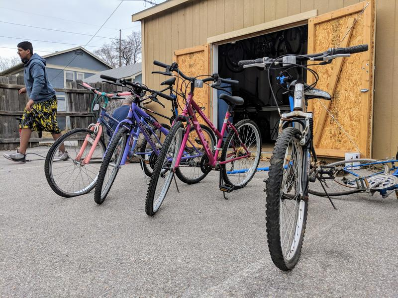 A row of bikes sits outside of the Bike Shed at the Opportunity Zone. Dalton, 18, gets up to find a tool