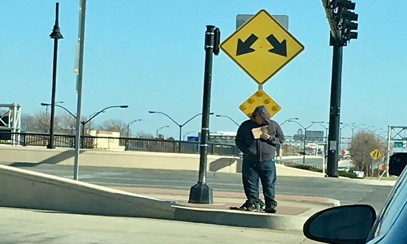 A man holds a sign while panhandling at an intersection in Wichita. Two new ordinances aim to curb panhandling in the city.