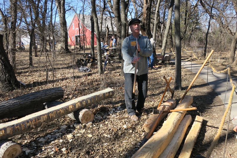 Nate Dyck shows how he squares logs. The logs will eventually be built into a structure at Kauffman Museum In North Newton.