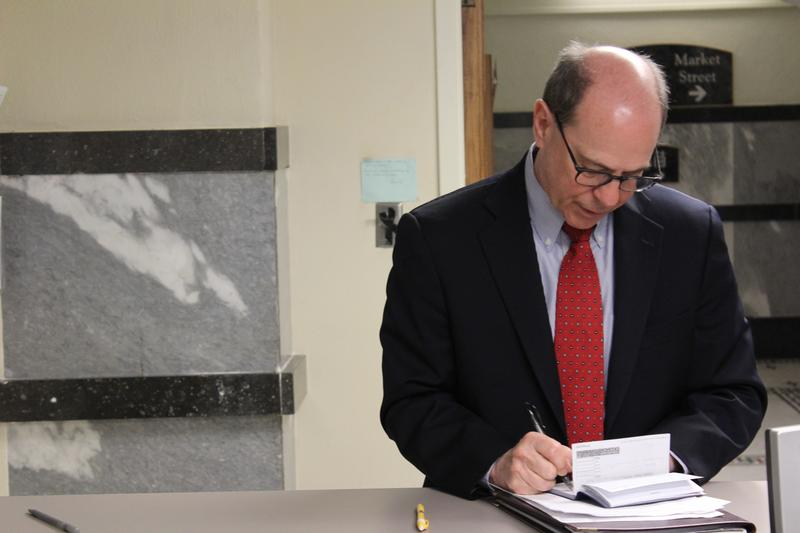 Steve Brunk writes a check for a filing fee to run for a seat on the Sedgwick County Commission.