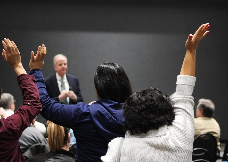 Immigration activists raise their hands at Sen. Jerry Moran's recent town hall meeting in Wichita. They're pushing for a bill that doesn't limit legal immigration in exchange for protection for Dreamers.