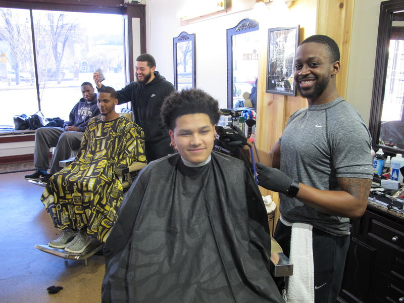 Left to Right: Joshua Mann, Barber Sean Rigsby (standing), Mykeyus Woods, Barber/Owner of Artistry Lounge,  Jeremie Mcglory (standing) and Ihsan McCoy