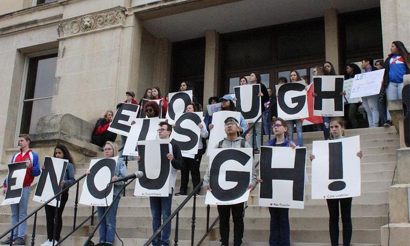 "Students spell out ""enough is enough"" on the steps of the old courthouse in downtown Wichita. Each sign bore the name of a person killed in last month's school shooting in Parkland, Florida."