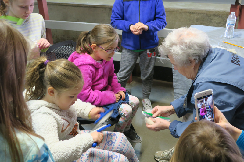 Children learn how to brush the wool fibers using two brushes.