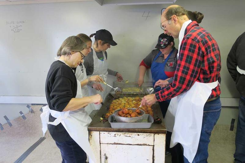 Volunteers take two-hour shifts frying New Year's Cookies, a glazed fried dough ball with raisins.