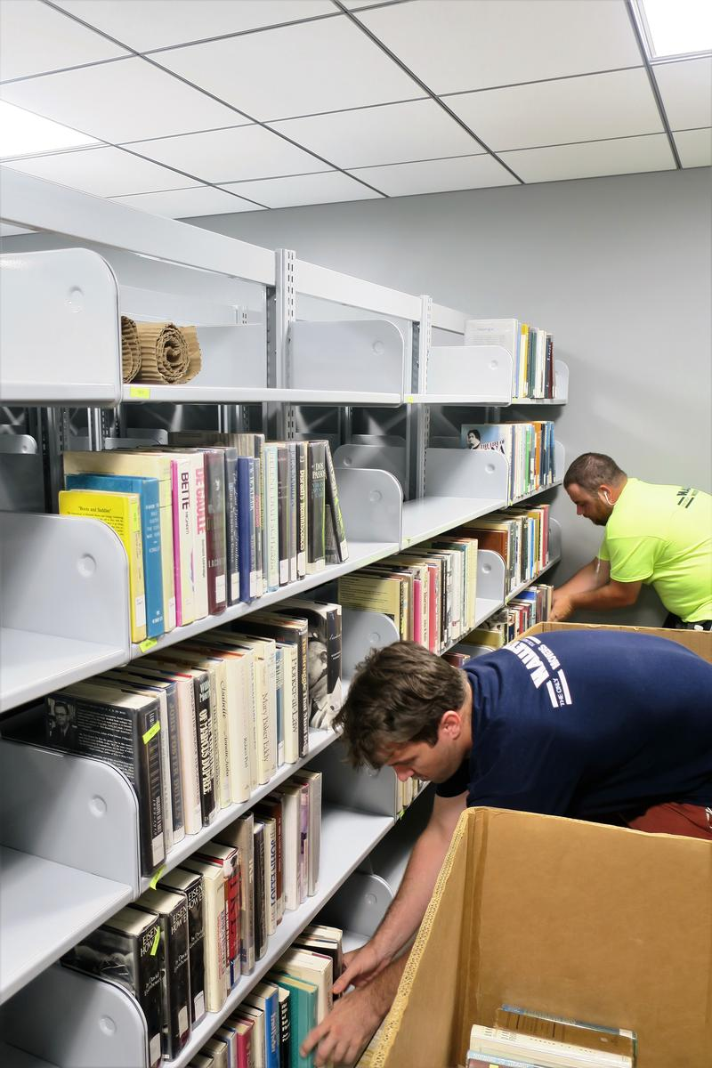 A moving crew unpacks and reshelves books and materials in the Advanced Learning Library.