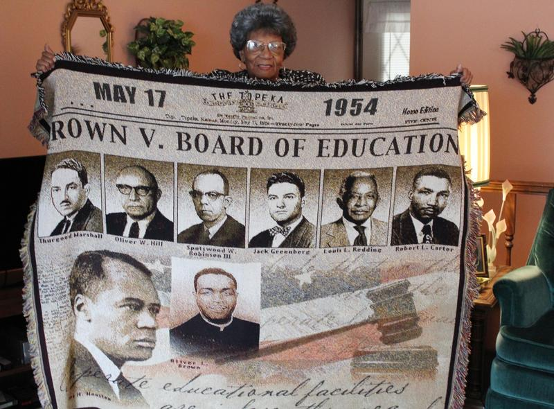 Leola Brown Montgomery holds up a blanket illustrating the Brown v. Board of Education of Topeka case. Her husband the late Oliver Brown was the lead plaintiff in the civil rights case.