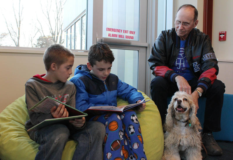 Andon Shriver, left, and a friend read at the Mulvane Public Library while Barney and his owner, Dave Peebler, listen.
