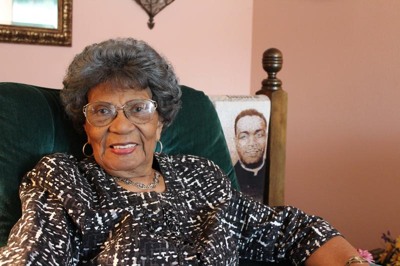 Leola Montgomery Brown sits in her living room next to a blanket depicting Brown v. Board of Education. Her husband, Oliver Brown, seen behind her, was the lead plaintiff in the case.