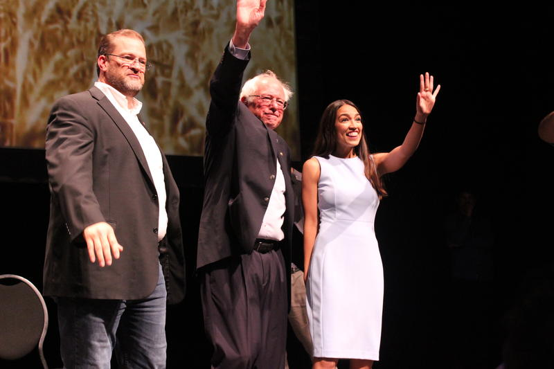 Thompson, Sanders and Ocasio-Cortez wave to the crowd after Sanders' speech before exiting the stage.