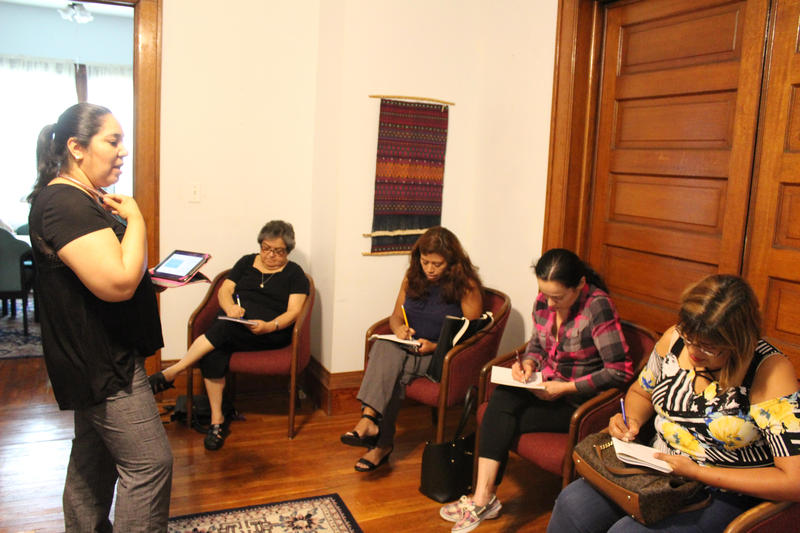 Activist Claudio Amaro teaches a group of Hispanic women about the voting process.
