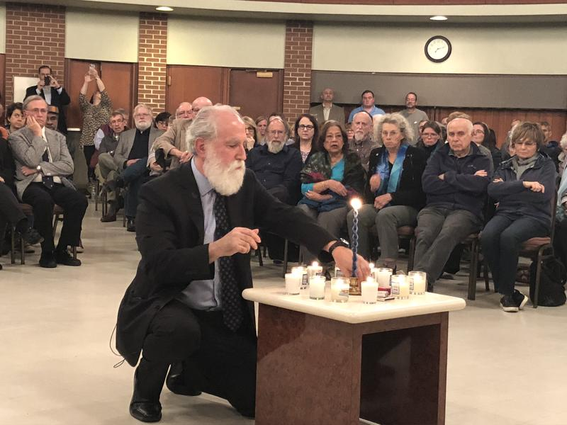 Rabbi Michael Davis of Congregation Emanu-El uses a ceremonial havdalah candle to light 11 candles in memory of the Pittsburgh synagogue shooting victims.