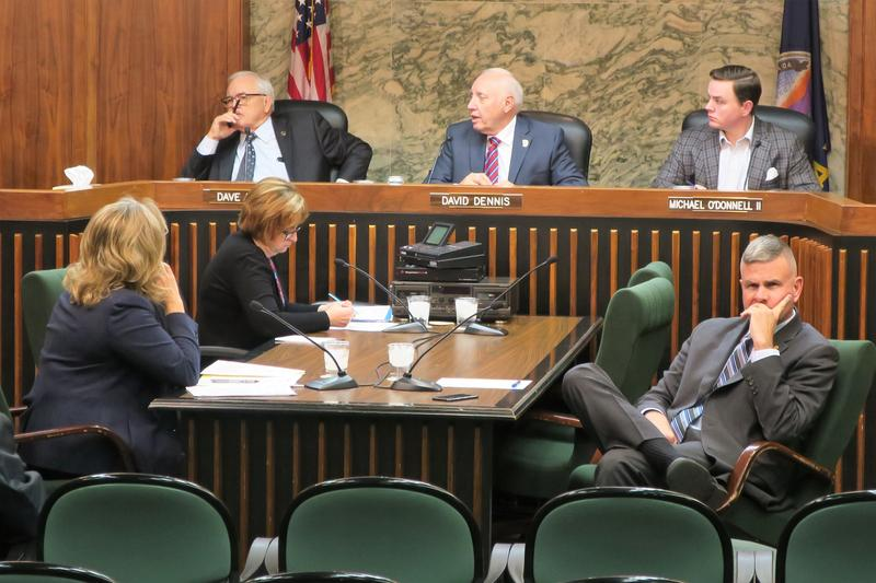Former County Manager Michael Scholes, bottom right, turns his back toward commissioners during a meeting last month.
