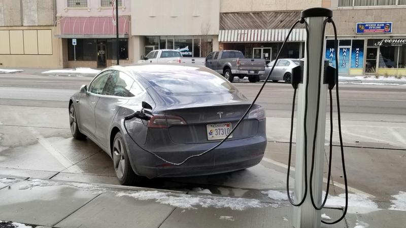 An electric vehicle fuels up at a charging station in downtown Topeka.