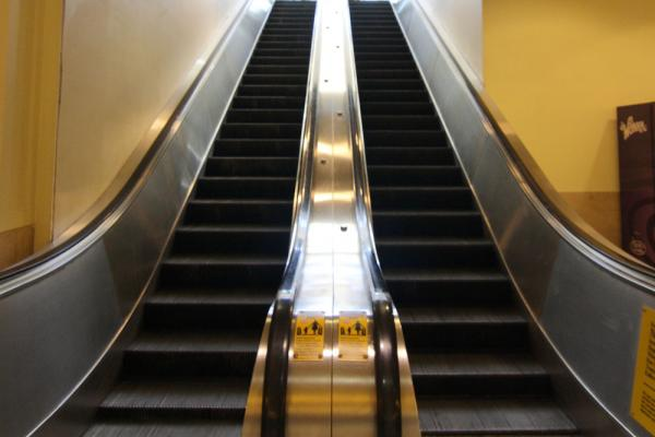 "The word ""escalator"" was a trademark of the Otis Elevator Company, who used it to describe the wooden-stepped model they displayed at a Paris Exposition in 1900."