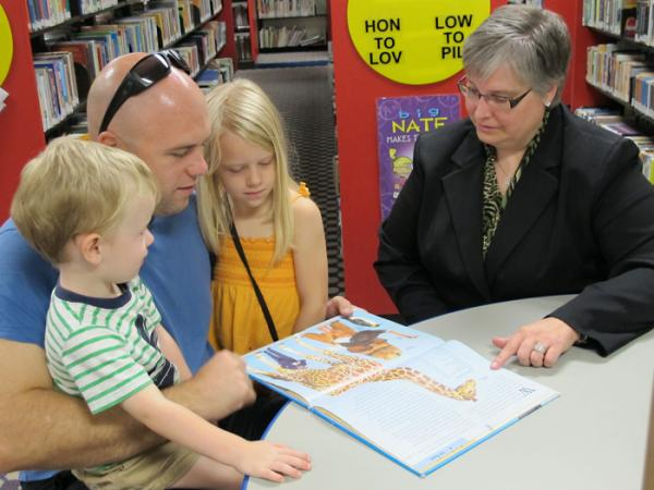 Cynthia Berner Harris, director of libraries for the Wichita Public Library, sits with Joel Potter and his children, Emeth and Sela, in the children's room at the central library.