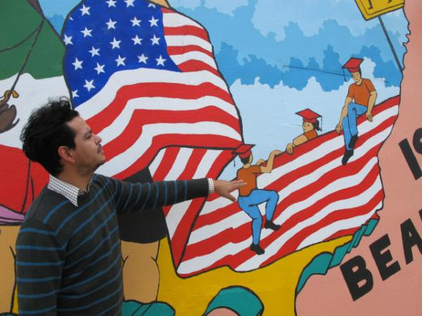 Armando Minjarez explains a piece of the new mural that depicts a U.S. - Mexico border made out of United States flag.