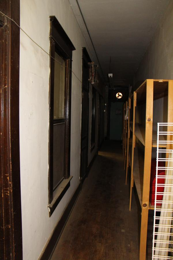 The upstairs hallway separating two interior-facing apartments above Central Plains Novelty. The staff reports hearing footsteps up here, when the area is empty.