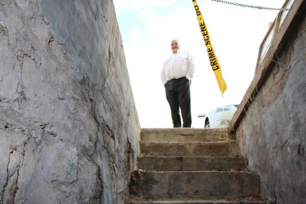 "Scott Bell stands at the top of the basement steps at Accent Bridal & Tux. Bell says the ""creepy"" basement is hand-dug and full of local limestone rock."