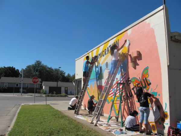 South High students paint a mural depicting the immigration story near 21st Street and Park Place.