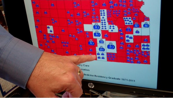 Dr. Rick Kellerman points out blue bags on a map of the US. Each bag stands for doctors trained at KU Med School in Wichita. Without these bags virtually the entire state becomes under-served.