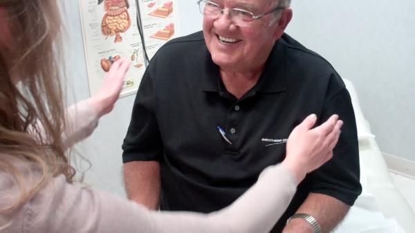 KU Med School student Rachel Svaty examines Belleville, Kan. resident Mr. McChesney's sore hand.