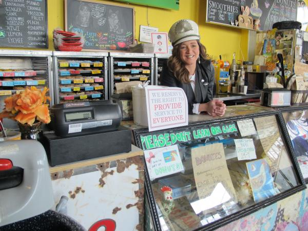 Angela Mallory behind the counter of the donut shop she owns with her business partner, Michael Carmody