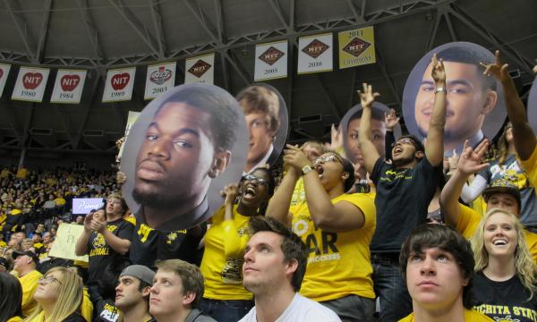"Shocker fans fill ""The Roundhouse"", some hold large photos of starters (L to R) Chadrack Lufile, Ron Baker, Cleanthony Early and Fred VanVleet."