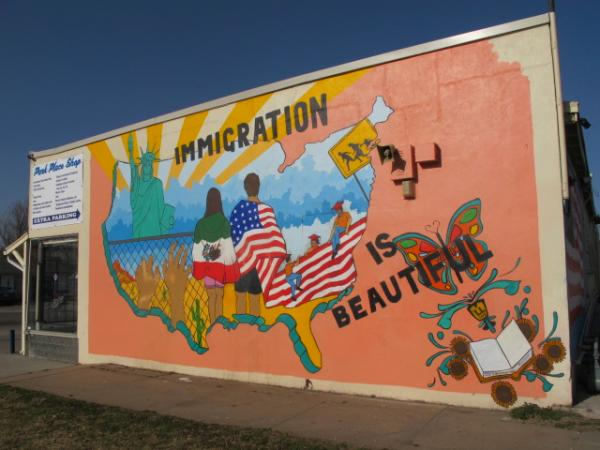 "The ""Immigration is Beautiful"" mural after its second restoration. A security camera has also been installed to catch future vandals."