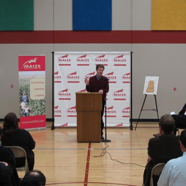Kansas Governor Sam Brownback speaks before a crowd inside the Vermillion Elementary School gym. Brownback stopped at the school to spread his message that state-funded all-day kindergarten is needed across the state.