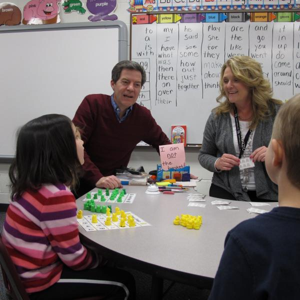 Gov. Sam Brownback, alongside Kindergarten Teacher Pam Wood, helps students to play math bingo in a classroom at Vermillion Elementary School. Brownback toured the elementary school's kindergarten facilities on Tuesday afternoon.