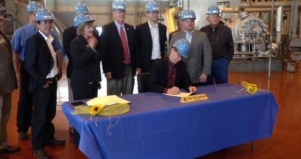 Gov. Sam Brownback signs copies of HB 2636 at Holcomb Generating Station