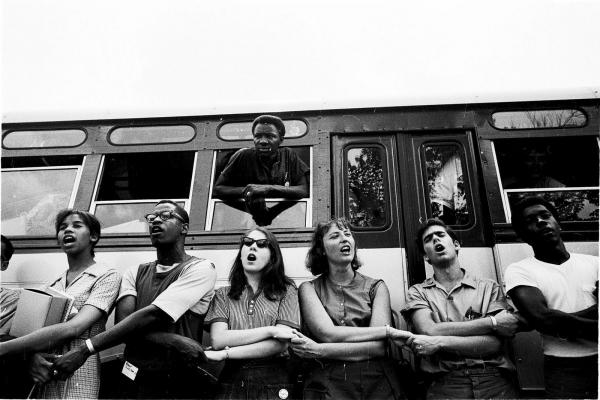 Volunteers link arms and sing freedom songs before boarding the bus for Mississippi. Photograph by Ted Polumbaum.