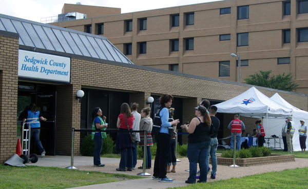 A small line forms for free MMR (Measles, Mumps, Rubella) vaccines at the Sedgwick County Health Department office.