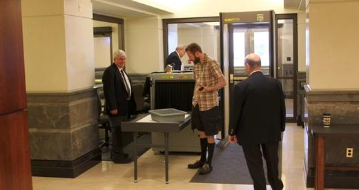 A visitor to the Kansas Statehouse going through security.