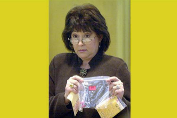 Sedgwick County (Kan.) District Attorney Nola Foulston holds a plastic bag containing hair clips worn by the sole survivor of a quadruple killing, during the trial of the brothers who are charged in the killings, in a courtroom in Wichita, Kan., Wednesday, Oct. 9, 2002.
