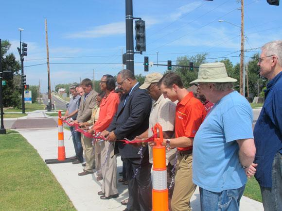 City officials celebrate the completion of the improvements on 13th Street between Hydraulic and Oliver during a ribbon cutting on Friday.